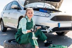 H?rlig mekaniker med skiftnycklar som ?ndrar gummihjul i bil arkivfoto