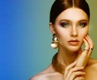 H?rlig modemodell som b?r eleganta smycken i f?rgljus arkivbild