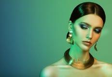 H?rlig modemodell som b?r eleganta smycken i f?rgljus fotografering för bildbyråer