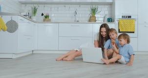 H?rlig modern ung familj som hemma ligger p? golvet och g?r n?got i b?rbar dator stock video