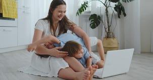 H?rlig modern ung familj som hemma ligger p? golvet och g?r n?got i b?rbar dator arkivfilmer