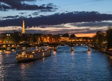 H?rlig natt Paris, brusandeEiffeltorn, bro Pont des Arts ?ver floden Seine och touristic fartyg france arkivbilder