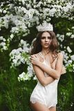 H?rlig och sexig ung modellkvinna med den perfekta kroppen i stilfull damunderkl?der med kronan p? hennes huvud som poserar under arkivfoto