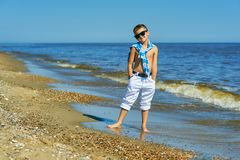 H?rlig pojke som poserar p? sj?sidan p? en solig sommardag royaltyfri bild