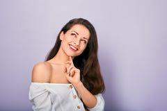 H?rlig positiv ung tillf?llig kvinna med handen under framsidan som t?nker och ser upp i den vita skjortan p? purpurf?rgad bakgru royaltyfria bilder