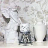 h?rlig sammans?ttning En statyett ?r en ?ngel, en tillbringare och en vas royaltyfria foton