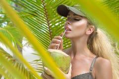 H?rlig sexig flicka i bikinin som poserar p? den karibiska stranden och rymmer en kokosn?t royaltyfri fotografi