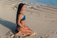 H?rlig sexig flicka med l?ngt h?r i bl? bikini som placerar p? stranden med vit sand royaltyfri fotografi