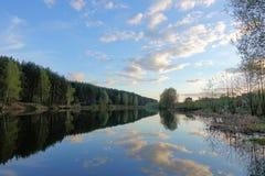 H?rlig solnedg?ng p? skogsj?n oklarheter reflekterat vatten royaltyfri bild