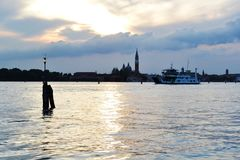 H?rlig solnedg?ng ?ver den Venedig lagun, cloudscape, cityscape av ?n av San Giorgio Maggiore och en f?rjakorsning fj?rden arkivfoto