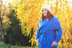 H?rlig h?stkvinna utomhus fashion kvinnan Parkerar det iklädda blåa laget för den unga kvinnan och varma hatten som går i höst h? royaltyfria foton