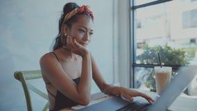 H?rlig ung asiatisk flicka som arbetar p? en coffee shop med en b?rbar dator Kvinnlig freelancer som arbetar i coffee shop lager videofilmer