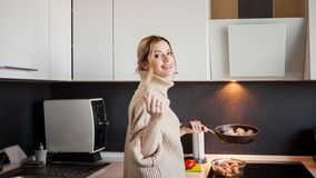 H?rlig ung blondin som rymmer en stekpanna f?r att starta laga mat, sj?lv-matlagning sund mat arkivfoto