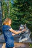H?rlig ung dam med hennes f?rtjusande gulliga hund av den siberian hasky aveln i sommarskog p? solnedg?ngen Lycklig ton?rs- flick arkivbild