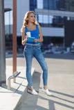 H?rlig ung flickainnehavanteckningsbok och kopp av coffe som st?r p? gatan begrepp av aff?rs- eller utbildningslivsstilen fotografering för bildbyråer