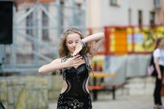 H?rlig ung kvinna i kl?der f?r en tillf?llig stil som isoleras ?ver vit bakgrund Ung flicka som offentligt dansar, arabisk dans,  arkivfoto