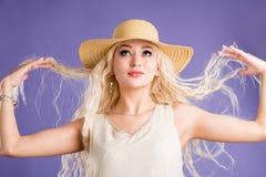 H?rlig ung kvinna i solhatt p? purpurf?rgad bakgrund royaltyfri fotografi
