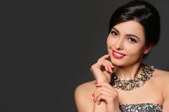 H?rlig ung kvinna med eleganta smycken p? m?rk bakgrund royaltyfria bilder