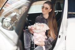 H?rlig ung kvinna som mycket sitter p? f?rars?tet i en bil med en rosa ask av mjukt, vitt, med en rosa list av tult-s?nkan arkivfoton