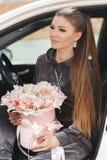 H?rlig ung kvinna som mycket sitter p? f?rars?tet i en bil med en rosa ask av mjukt, vitt, med en rosa list av tult-s?nkan arkivbilder