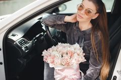 H?rlig ung kvinna som mycket sitter p? f?rars?tet i en bil med en rosa ask av mjukt, vitt, med en rosa list av tult-s?nkan royaltyfri foto