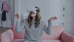 H?rlig ung kvinnlig spela lek i vrexponeringsglas Kvinna som anv?nder h?rlurar med mikrofon f?r virtuell verklighet 3D Hon sitter arkivfilmer
