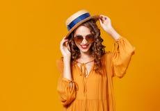 H?rlig ung lockig kvinna i sommarhatt och solglas?gon p? gul bakgrund royaltyfri foto