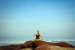 H?rlig ?vande yoga f?r ung kvinna och str?cknings?vningar p? sommarhavstranden arkivfoto