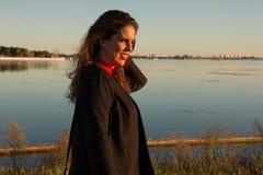 H?rlig yttersida f?r anseende f?r brunettkvinnast?ende i en solig dag, med en sj? i bakgrund royaltyfria foton