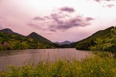 h?rliga liggande Sikt av blommor, grönt gräs, härliga sjöar, kullar och berg En härlig färg i bakgrunden arkivbilder