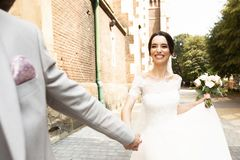 H?rliga nygift personpar g?r n?ra gammal kristen kyrka fotografering för bildbyråer