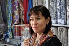 h?rligt kvinnabarn St?ende p? bakgrunden av textilprodukter royaltyfri fotografi