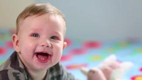 H?rligt le behandla som ett barn: Ett ursnyggt litet behandla som ett barn ligger p? s?ngen och leendena p? kameran med en trevli lager videofilmer