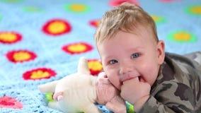 H?rligt le behandla som ett barn: Ett ursnyggt litet behandla som ett barn ligger p? s?ngen och leendena p? kameran med en trevli stock video