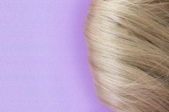 h?rligt h?r Ljus - brunt h?r Hår samlade i en bulle på en lila bakgrund med fritt utrymme f?r text För en affisch eller en affär royaltyfri fotografi