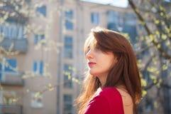 H?rligt slut upp st?enden av den unga brunettkvinnan med vinden som bl?ser h?r p? stads- bakgrund f?r byggnader arkivbilder