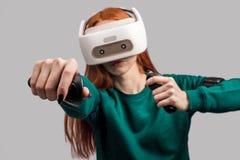 H?rlurar med mikrofon f?r virtuell verklighet f?r s?ker r?dh?rig mankvinna som b?rande siktar fr?n pilb?gen royaltyfri bild
