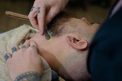 H?rstylist och barberare Fris?rer arbetar f?r en stilig grabb p? barberaren shoppar Barberaresax och rak rakkniv royaltyfri bild