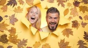 H?stlynnet och v?der ?r varma, och soligt och regn ?r m?jligt Lyckliga par, skäggig man och blond kvinna i guling royaltyfria bilder