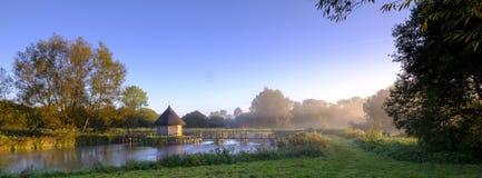H?stsoluppg?ng med mist p? ?lhusf?llorna p? flodprovet n?ra Longstock, Hampshire, UK royaltyfria bilder