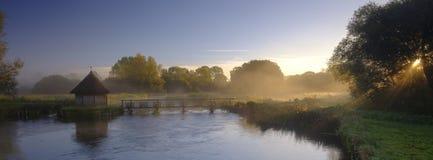 H?stsoluppg?ng med mist p? ?lhusf?llorna p? flodprovet n?ra Longstock, Hampshire, UK arkivfoton