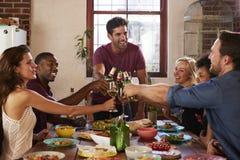 Hôte et amis faisant un pain grillé à un dîner Photographie stock