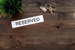 Hôtel de livre Exprimez les clés de pièce proches réservées sur le copyspace en bois sombre de vue supérieure de fond de table photographie stock