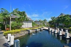Hôtel de tourisme classieux de luxe avec de l'eau coulant dans l'étang entouré par des pavillons photos stock