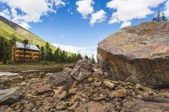 Hôtel en bois dans les montagnes près d'une grande roche photographie stock libre de droits