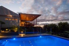 Hôtel moderne avec une piscine la nuit avec le ciel léger photographie stock