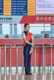 Hôtesse avec du charme devant le bureau à l'aéroport international capital de Pékin Images libres de droits