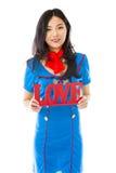 Hôtesse d'air asiatique stockant un texte rouge d'AMOUR Images stock