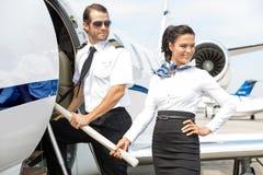 Hôtesse de l'air avec le pilote Boarding Private Jet Photographie stock