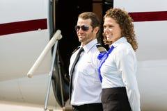 Hôtesse de l'air et pilote Looking Away Against privé Photographie stock libre de droits